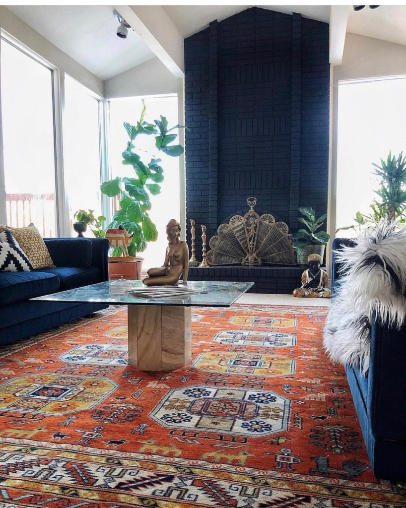 An Eclectic '70s Home Filled With Vintage Finds - Jenasie Earl   An eclectic living room filled with light and made unique with vintage finds. Double height windows and a dramatic black fireplace add substance to the living room.