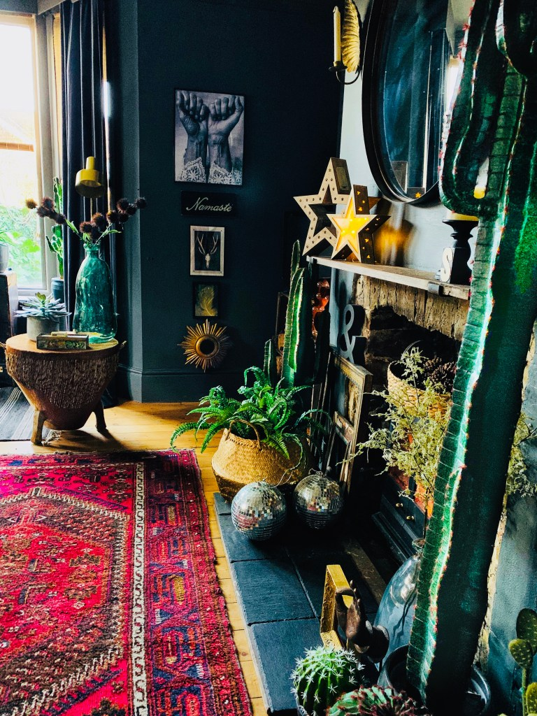 Bohemian, Dark & Inviting Home of Nadia Martini | Living room fireplace area. Boho and dark walls provide the backdrop to lush greenery, textures and vibrant colour pops.