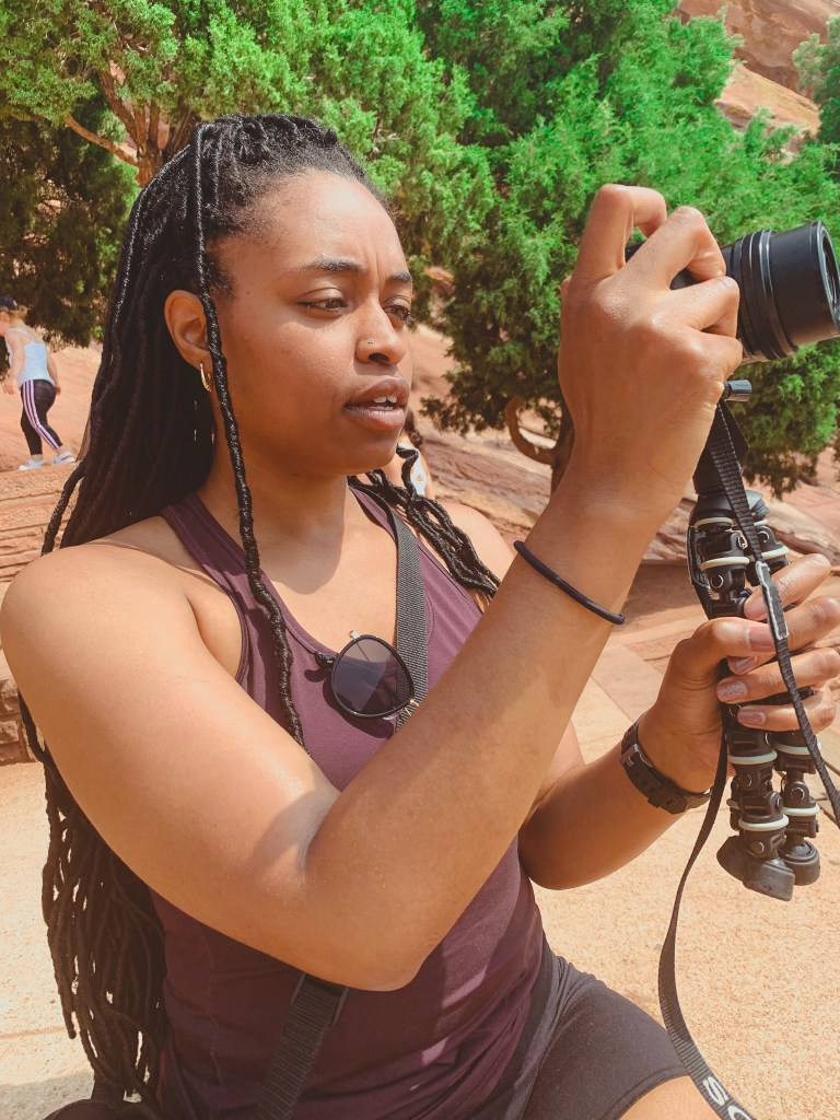 Black woman taking a photo at Red Rocks Park in Colorado