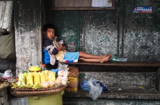 A young boy tends to their mango vending business in Baguio City, Philippines, while his mother is away for a while.