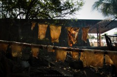 """Pieces of pork skins are left hanged on a wire line for it to be sun-dried before it will be cooked and turn it into okilas, similar to a """"chicharon"""", famous to locals. Okilas are sold for P15 (around 40 cents USD) per pack."""