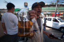 """A trader is seen selling a bottle of """"langis ng sawa"""" or """"oil of snake"""". He claims that by applying the snake's oil to a aching parts of the human body, it will help cure it. A bottle of this exotic product is sold at the streets for P3,500 ($79 USD) for one large bottle, can also be sold by smaller ones."""