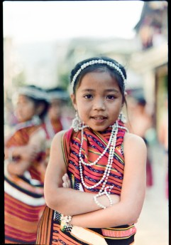 A young girl in her full traditional garb poses for photograph as she and her group awaits the start of the Lang-ay Festival grand street parade in Bontoc, Mountain Province, Philippines.