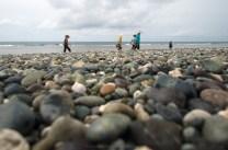Beach goers are seen along the pebble beach of Luna in La Union province.