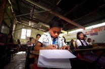 Grade six students are seen making their school work inside a dimly lit makeshift classroom built inside a basketball court at Baguio Country Club Village in Baguio City. Parents and Teachers' Association (PTA) made a joint movement to make an elementary school closer for 170 students to their homes back in 2007.