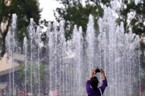 A tourist raises her camera as she attempts to photograph the newly partially installed water fountains at the Rose Garden in Burnham Park, Baguio City.