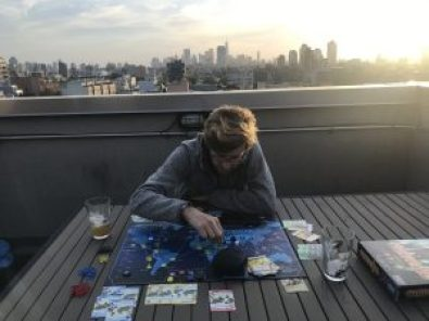 Man playing board game on a patio, New York skyline behind him