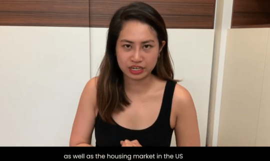 Woman in black tank top speaking to the camera about the housing market in the U.S.