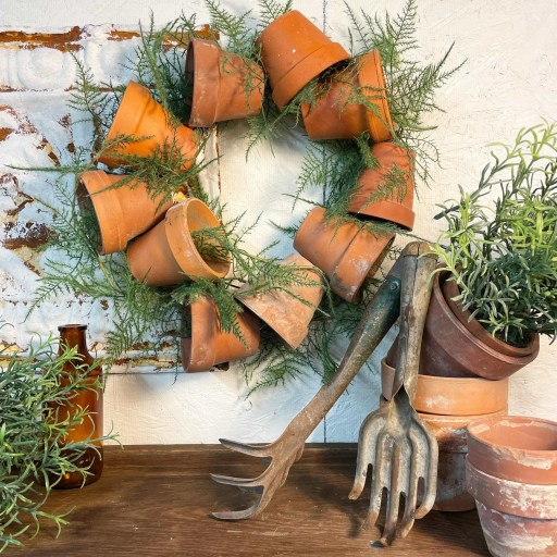 A wreath of terracotta pots. The pots are placed in a circle with plants. This piece of home decor is hung on a distressed brick wall.