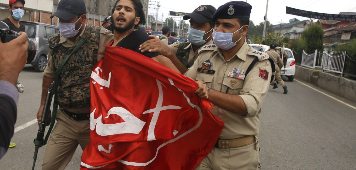 Police detains a Muharram mourner in Srinagar on Friday as a group of mourners…
