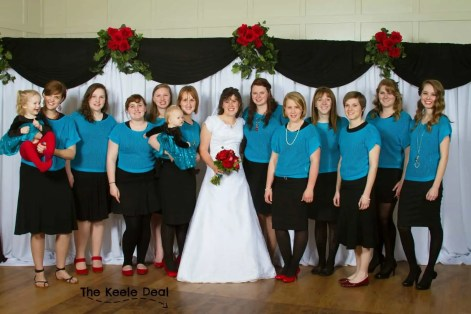 Bridesmaids wearing black, bright aqua blue and red!