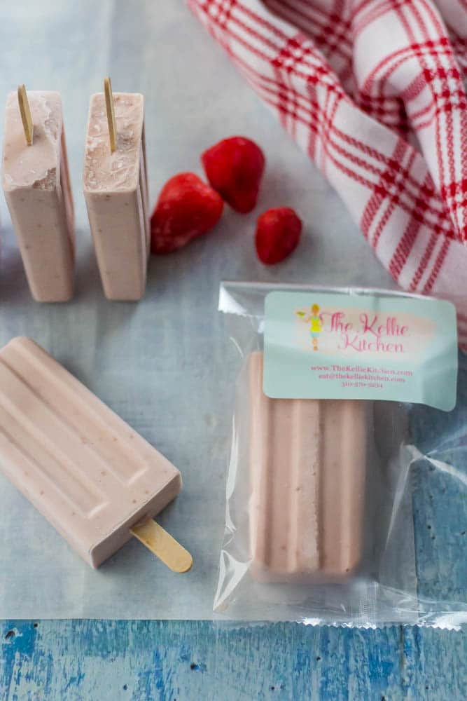 Pink frozen popsicles wrapped in clear plastic package on blue wood background. Strawberries scattered about. red white checked dish towel off to side.
