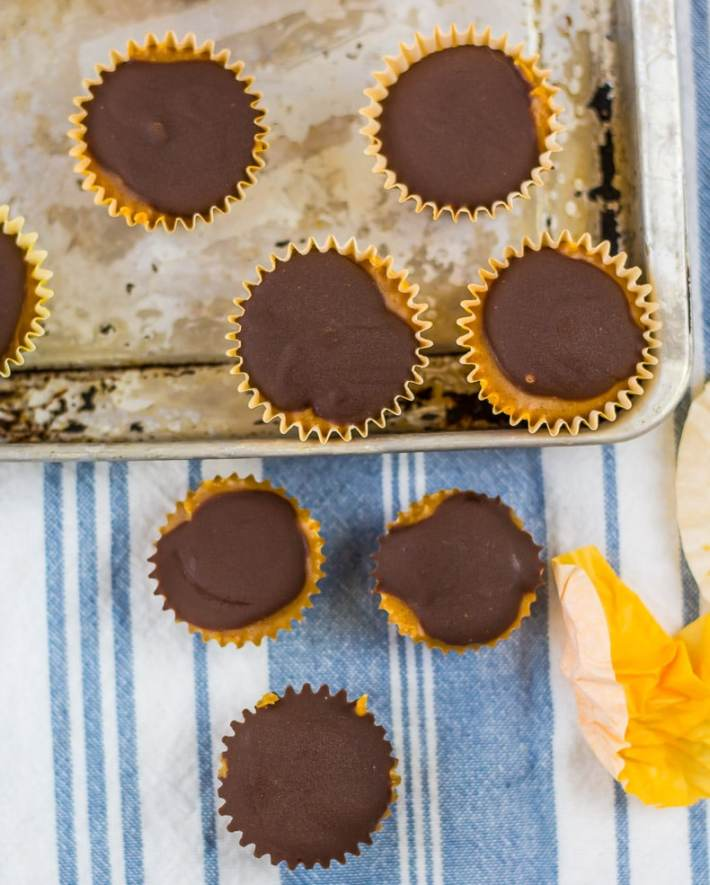 mini chocolate and tan cups on distressed metal tray. white and light blue striped towel in background laying flat.