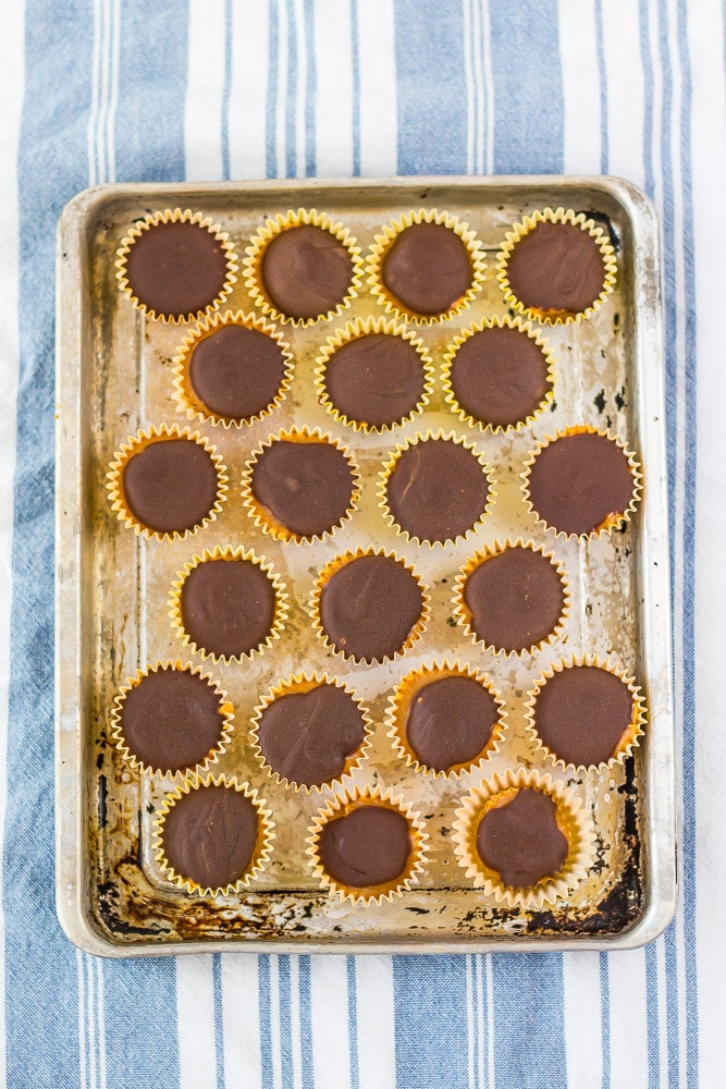 mini chocolate and Peanut Butter cups on distressed metal tray. white and light blue striped towel in background laying flat.