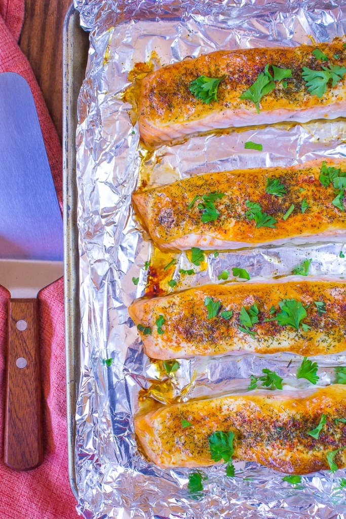 Baked Dijon Salmon. Pink filets with green parsley on top. Shiny tin foil lined baking sheet