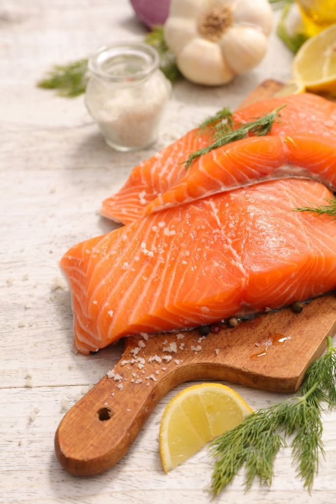 Raw salmon filets with seasonings shown and sliced lemon and green herbs.