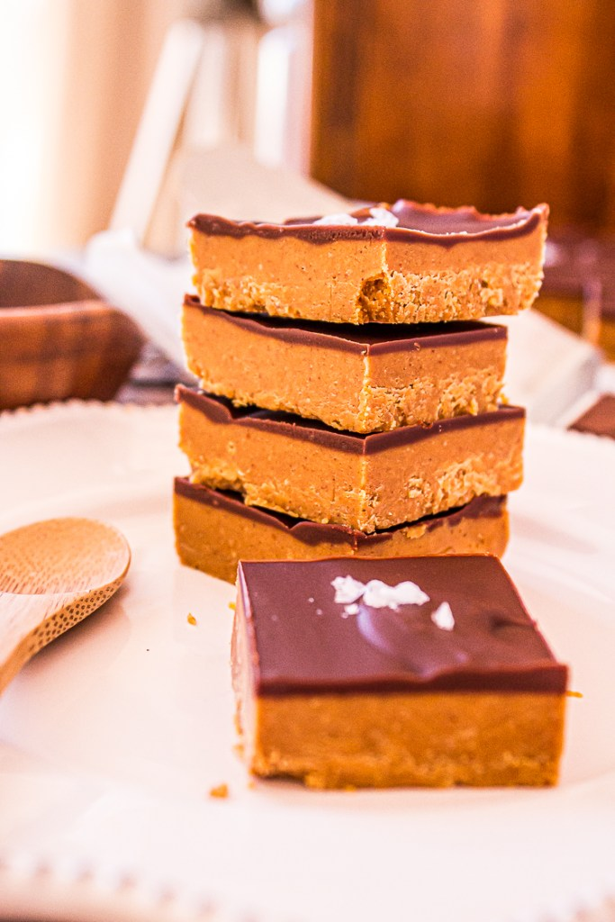 Tan brown peanut butter square dessert bar topped with dark brown chocolate on white plate. Stack of 4 bars in back.