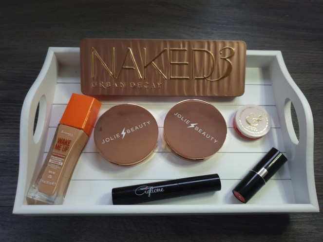 Festive Make Up Products Flatlay on a white wooden tray.