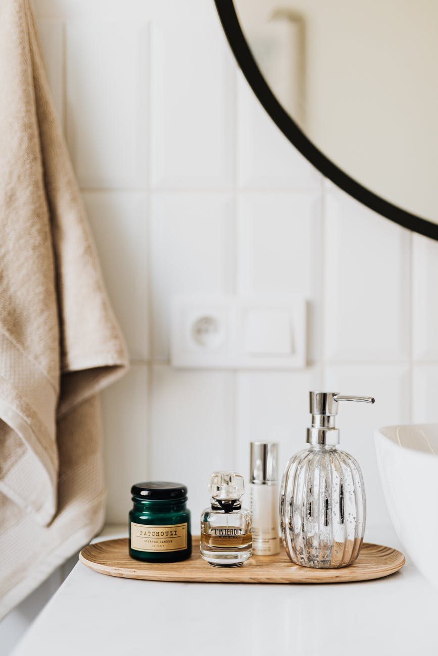 set of skincare supplies on white table in bathroom