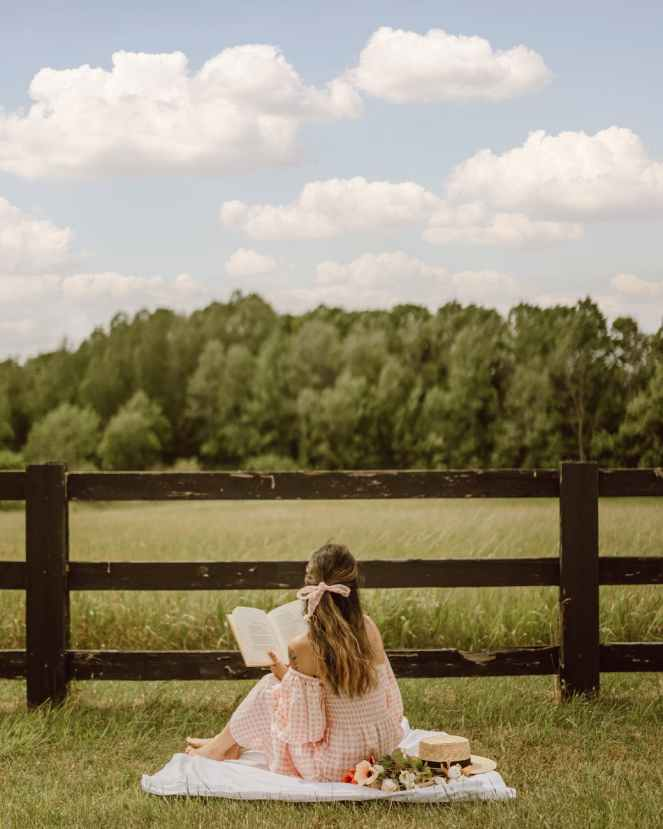 back view of a woman reading a book while sitting on a picnic blanket near the wooden fence for how reading can improve your mental health post.