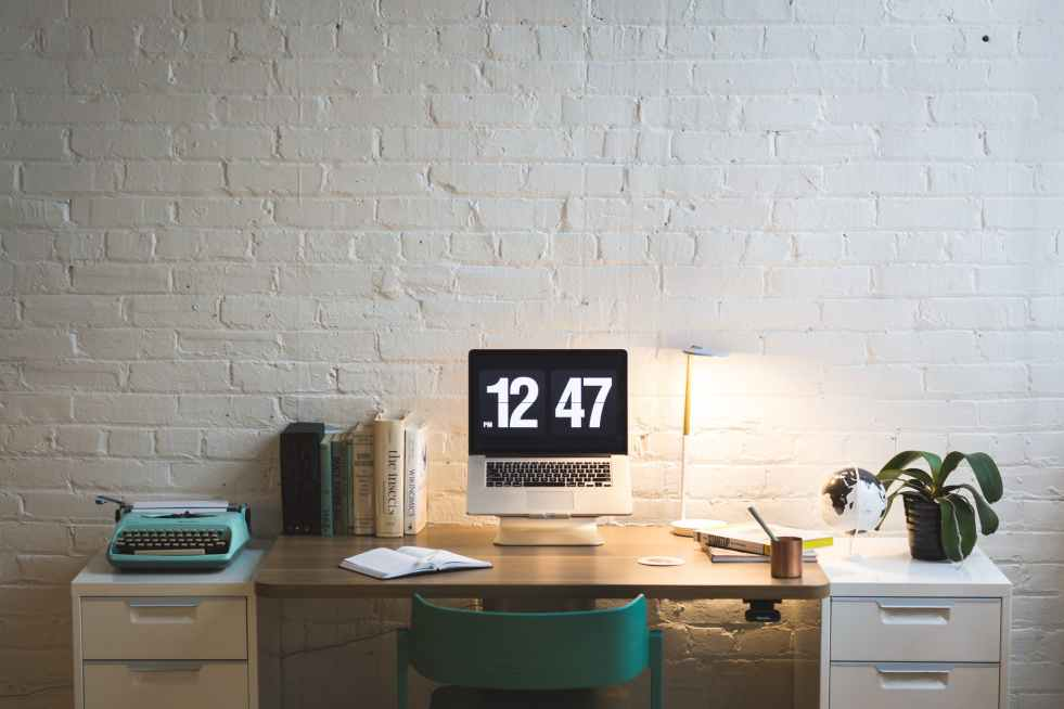 silver and black digital alarm clock on table