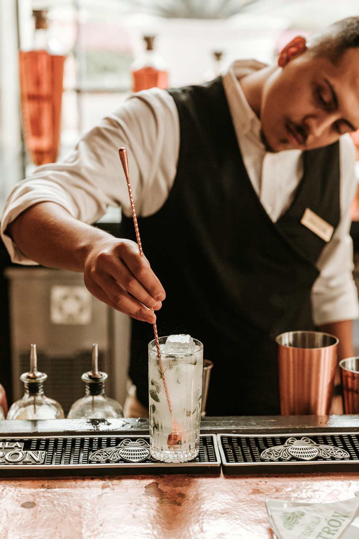 man stirring cocktail