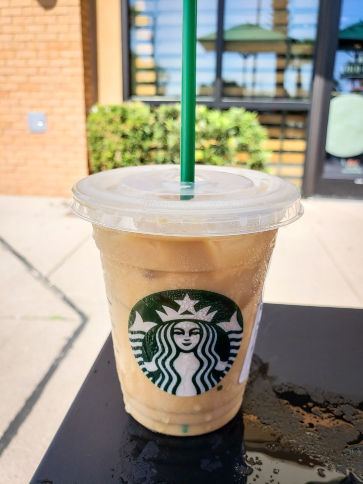 picture of a starbucks iced coffee with heavy whipping cream out side on a table