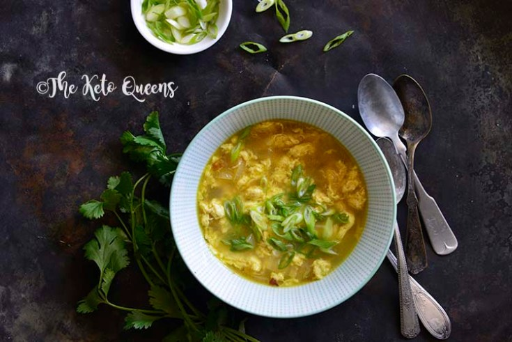 Horizontal picture of egg drop soup over head shot with scallions and spoons on a dark surface