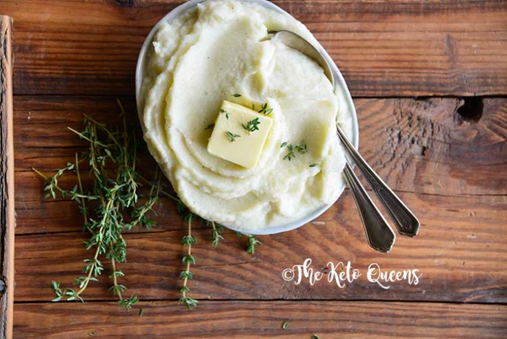 Horizontal image of mashed cauliflower in a bowl with butter, thyme and 2 spoons