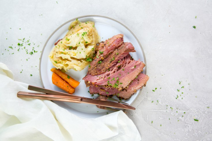 vertical image of corned beef, cabbage and carrots on a white plate with rose-colored fork and knee with napkin