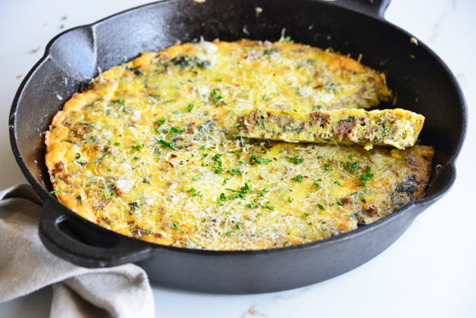 horizontal image of a baked frittata in a cast iron skillet close up with a white fabric napkin