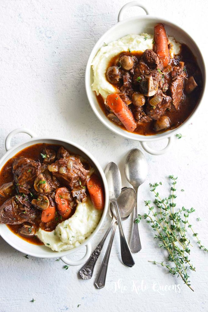 vertical image of 2 low carb instant pot beef stew in a white bowl with 3 spoons and fresh herbs on a white background