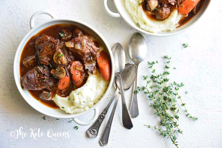 horizontal image of 2 low carb instant pot beef stew in a white bowl with 3 spoons and fresh herbs on a white background