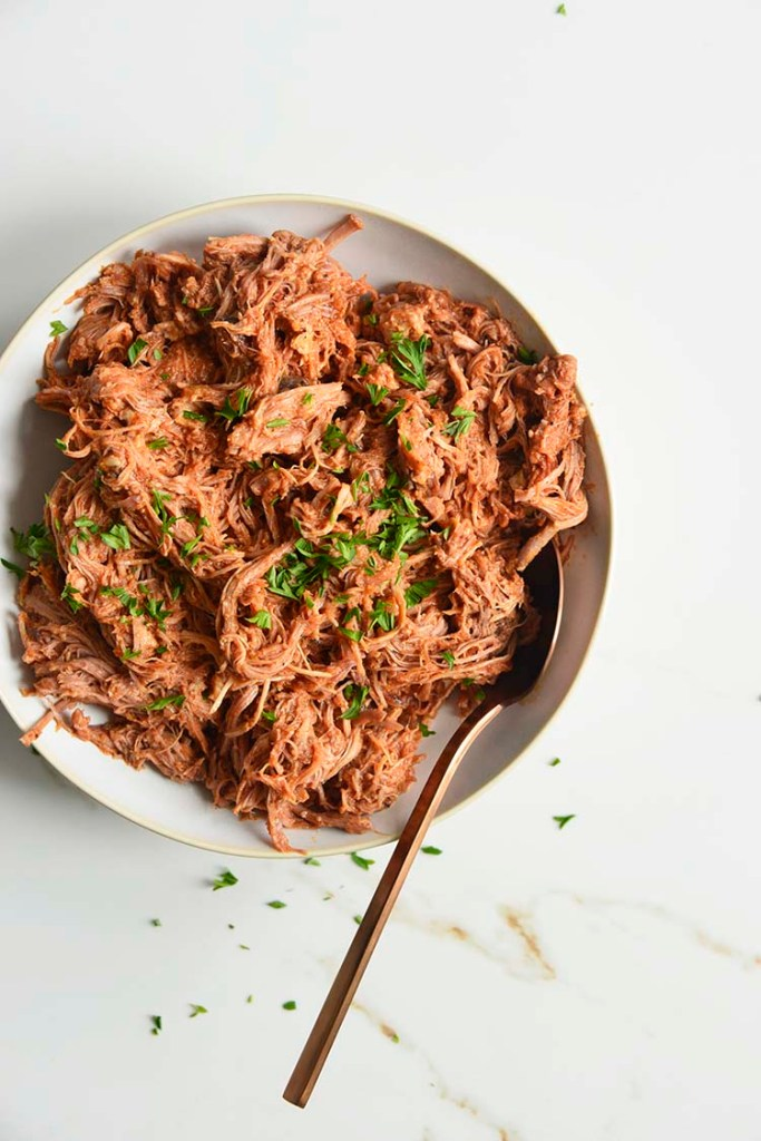 keto bbq pulled pork on a white bowl with parsley