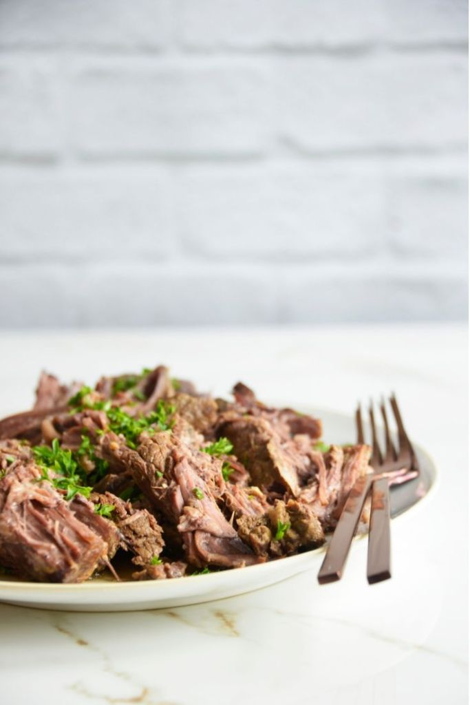 Pulled instant pot chuck roast with parsley and 2 forks on a white plate