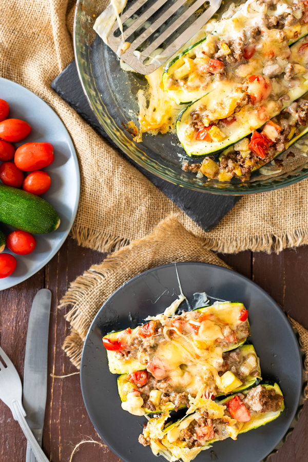slow cooker BBQ brisket stuffed zucchini boats on dark plates with a side of tomatoes