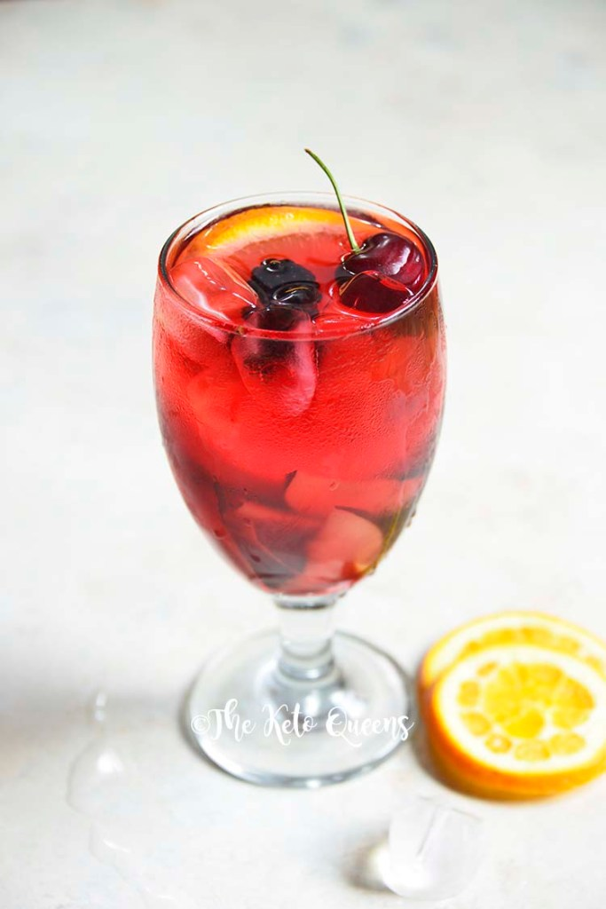 keto sangria mocktail recipe in a clear glass garnished with cherries and orange slices