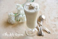 homemade vanilla bean keto milkshake in a tall glass with spoons and white flowers