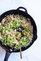 cauliflower fried rice in a cast iron skillet with a spoon