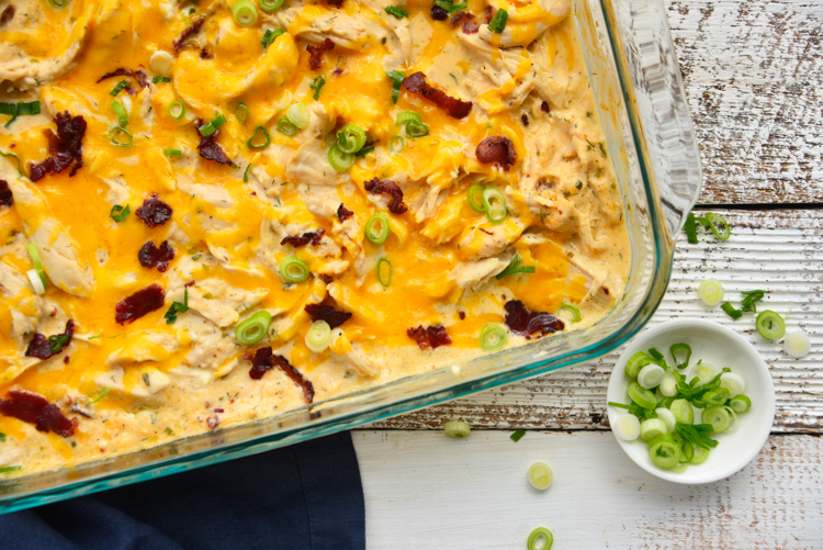 fully baked chicken topped with shredded cheddar cheese, bacon, and scallions in a glass baking dish