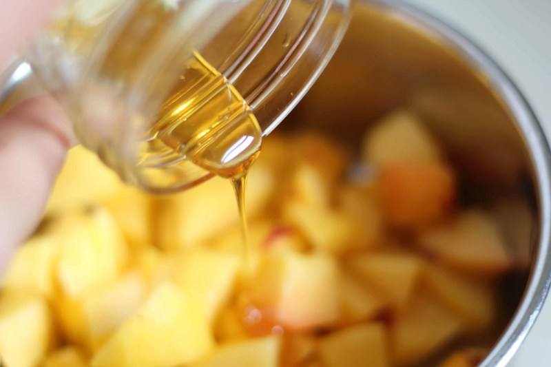 peaches in pot with honey drizzled on top