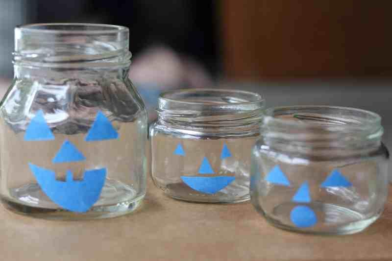 pumpkin jar faces using painter's tape on glass jars