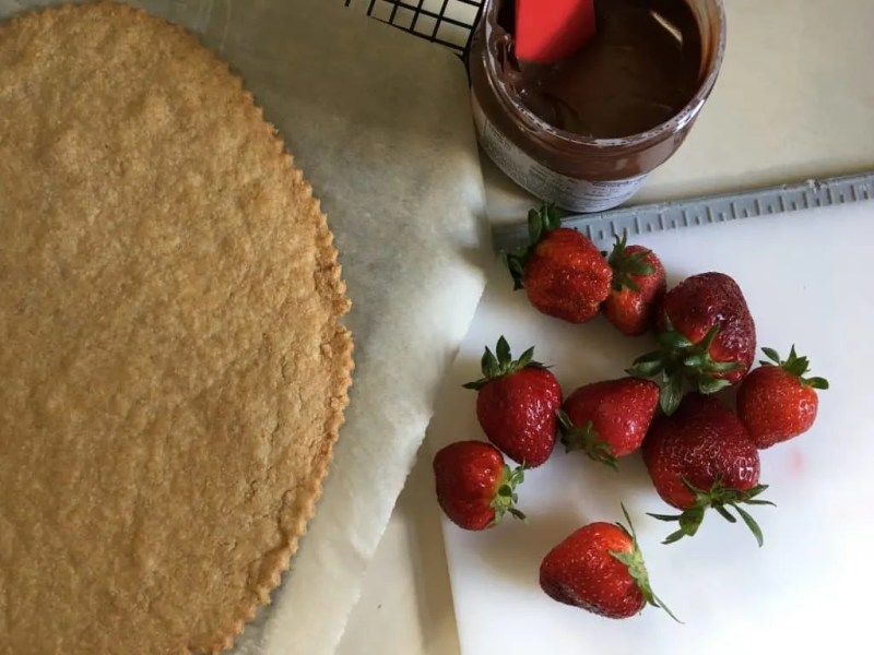 Freshly baked pie crust with strawberries and nutella on white cutting board