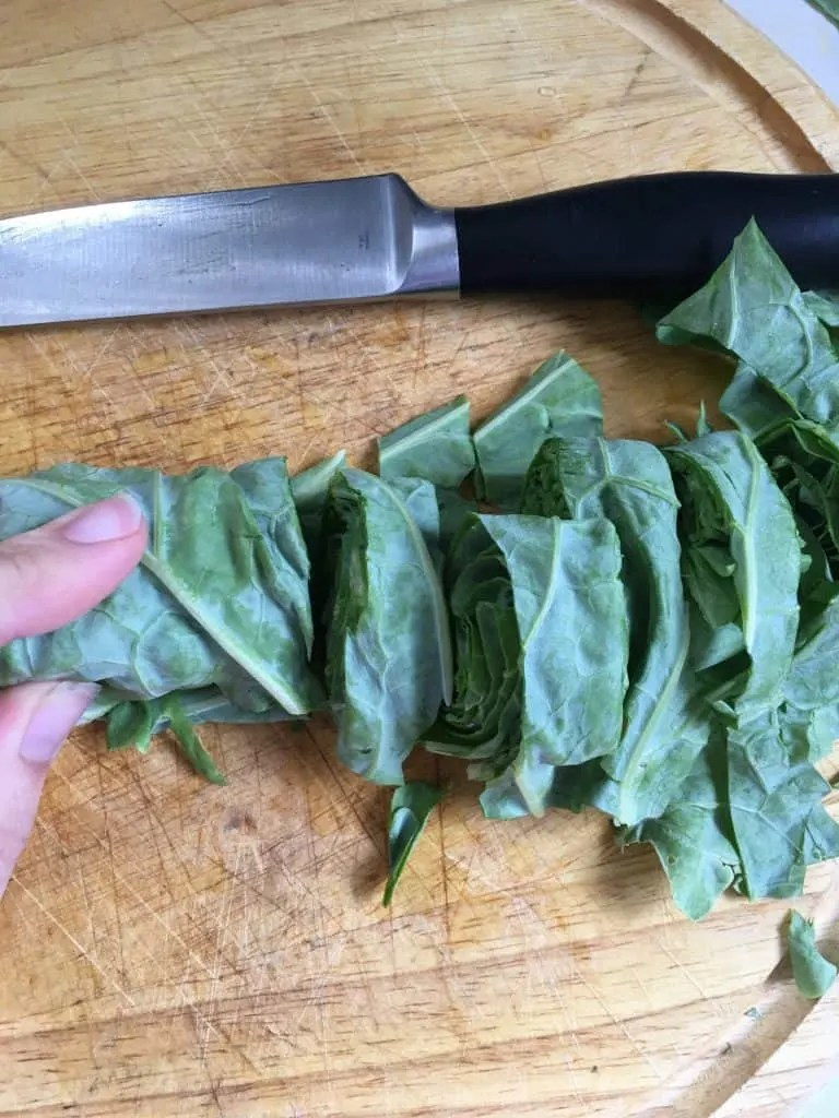 rolled and cut collard greens on wooden cutting board