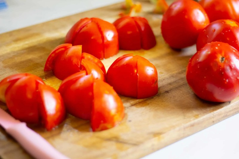 Quartered tomatoes on a wooden cutting board