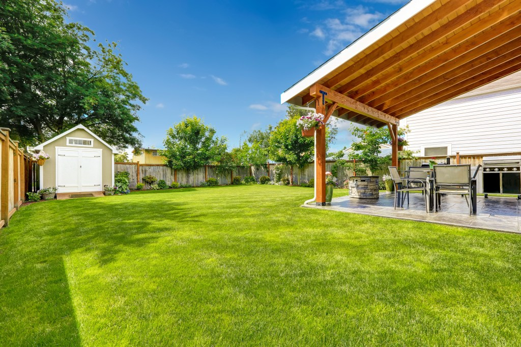 backyard space with green grass, shed with white doors and a covered patio