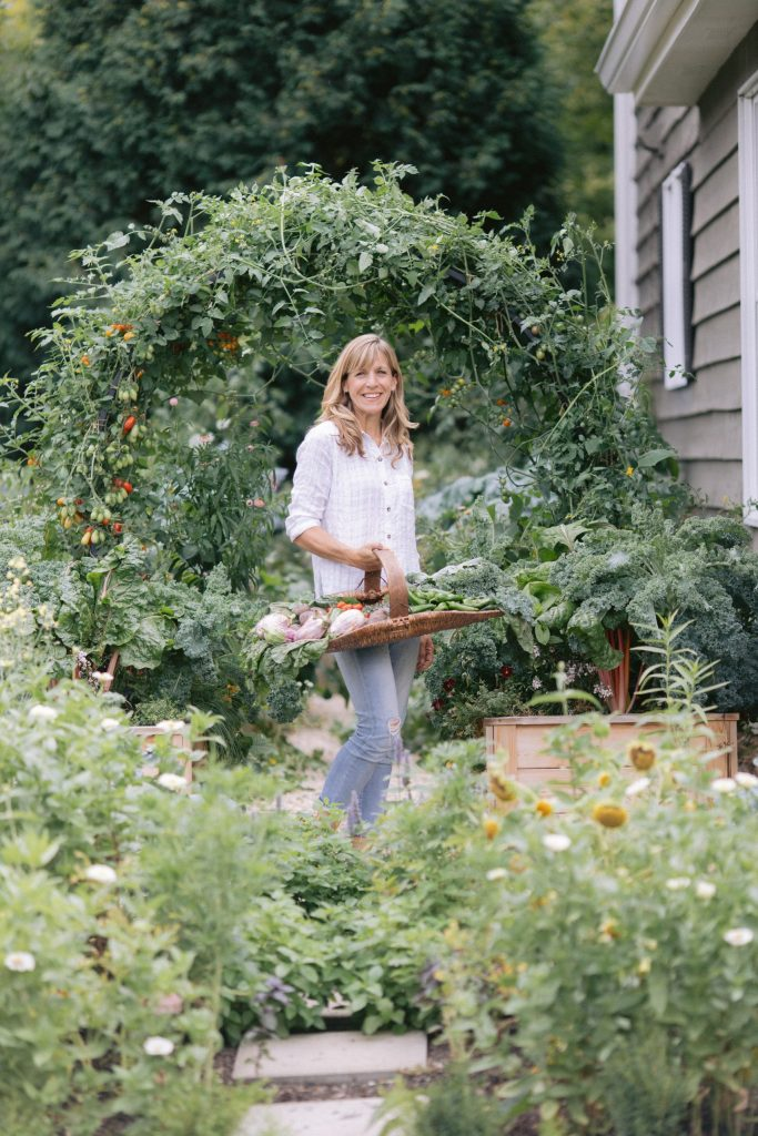 Nicole Burke of The Rooted Garden and Gardenary standing in her home garden