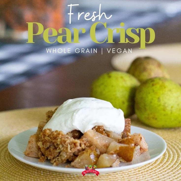 pear crisp topped with whipped cream on a white plate with fresh pears in the background