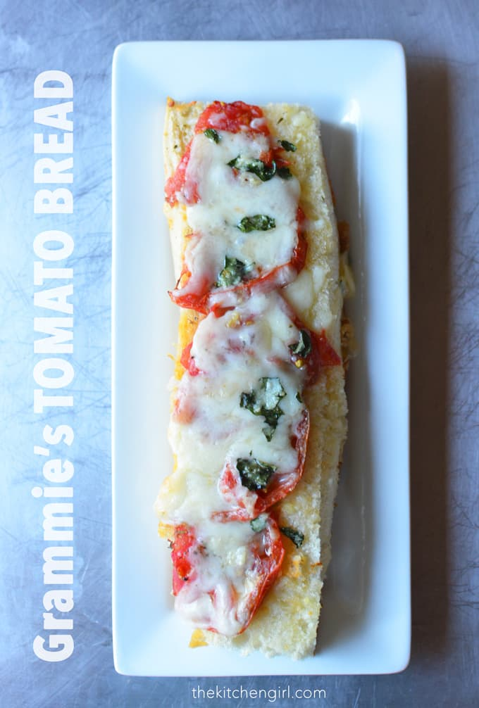 Cheesy garlic bread...with tomatoes and basil?! Yes plz! Grammie's Tomato Bread is a crowd pleaser for any occasion during tomato season. Easy comfort food! thekitchengirl.com