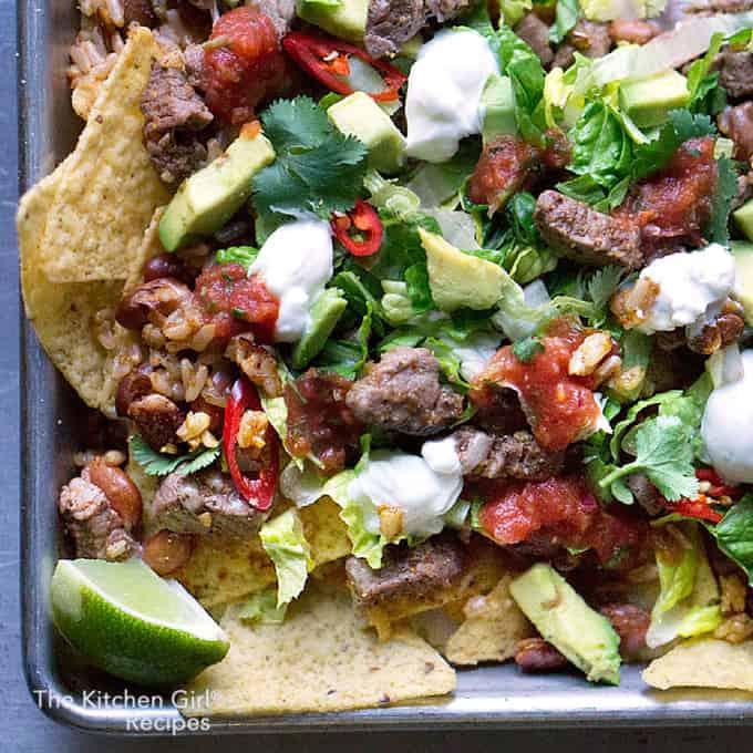 Cadillac nachos!! Made with steak, rice, beans, cheese, lettuce, avocado, cilantro, and peppers! Sheet Pan Steak Salad Nachos on thekitchengirl.com #cincodemayo #sheetpanmeal #sheetpannachos #healthynachos #healthymexican #gameday #glutenfree #nachos #tacosalad #filetmignon